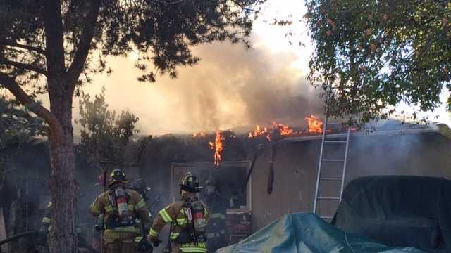 Sacramento Metro firefighters battle a blaze at two North Highlands homes on Tuesday, Nov. 10, 2015.
