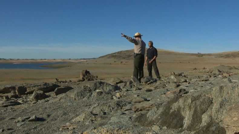 A state park ranger talks to Rep. Ami Bera on Thursday during a tour of the dry lake bed at Folsom Lake.