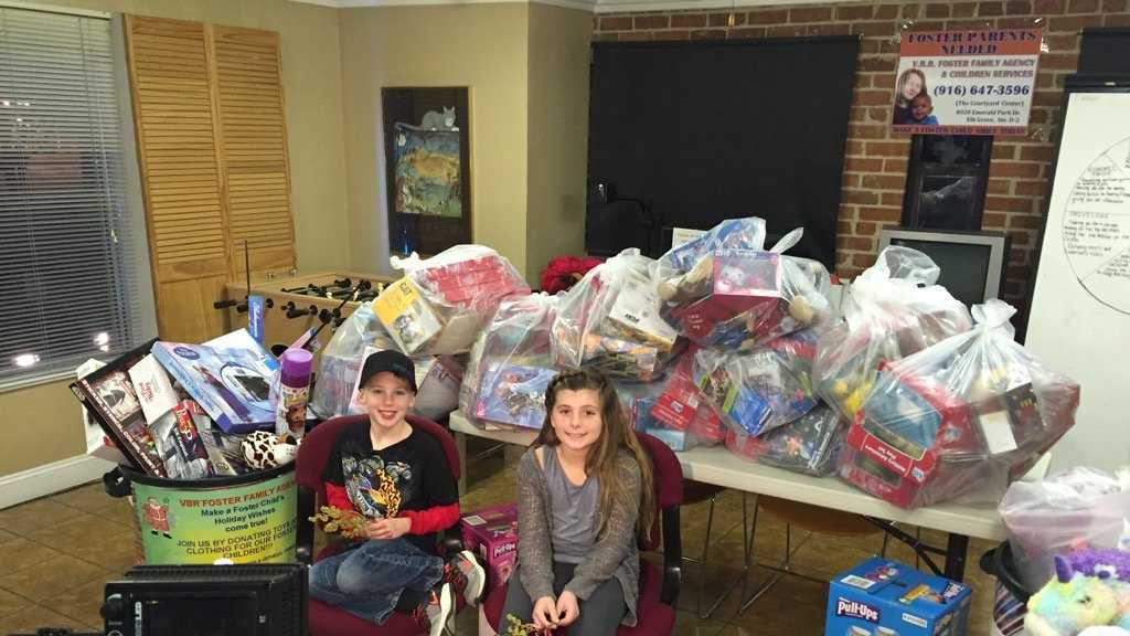 Danny Fry, 7, and Bailey Stone, 9, helped collect toys for the V.B.R. Foster Family Agency toy drive. The two children smile for the camera on Wednesday, Dec. 23, 2015, in front of the toys they collected so far.
