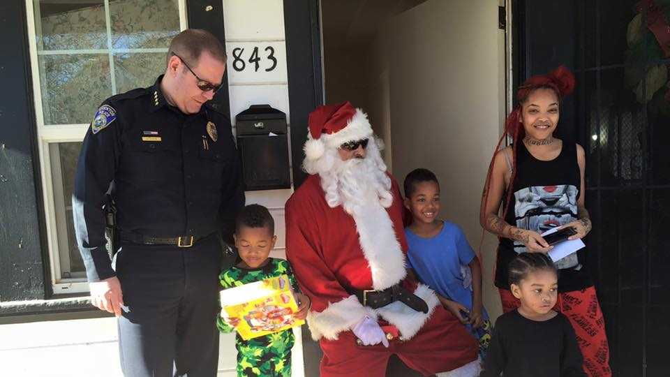 Stockton Police Chief Eric Jones poses with Santa and a family on Friday, Dec. 25, 2015. The Stockton Police Department delivered presents to families and children affected by violent crime this year.