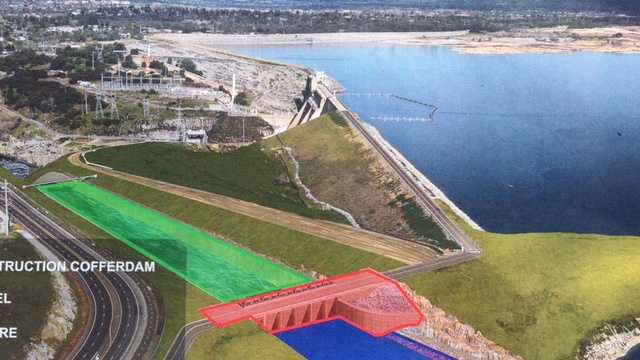 Water is now being held back by the new auxiliary dam (in red). Crews will soon begin removing the temporary construction dam (in yellow). By the end of the year, work will be complete on the downstream chute (in green.)