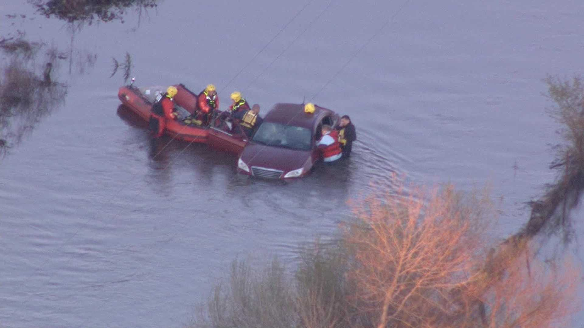 Crews rescue three people trapped in a car submerged in a flooded street on Monday, March 7, 2016.