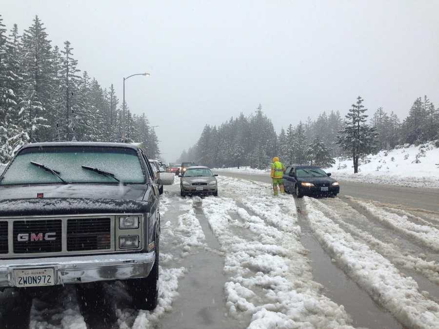 Chain installers install chains on vehicles as chain controls are in effect at Blue Canyon Sunday.