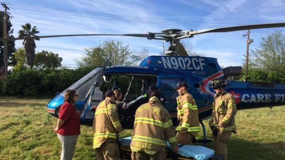 Sacramento Metro Fire crews assist a toddler who was being transported to UC Davis Medical Center on a helicopter after the aircraft made an emergency landing on Wednesday, March 23, 2016.