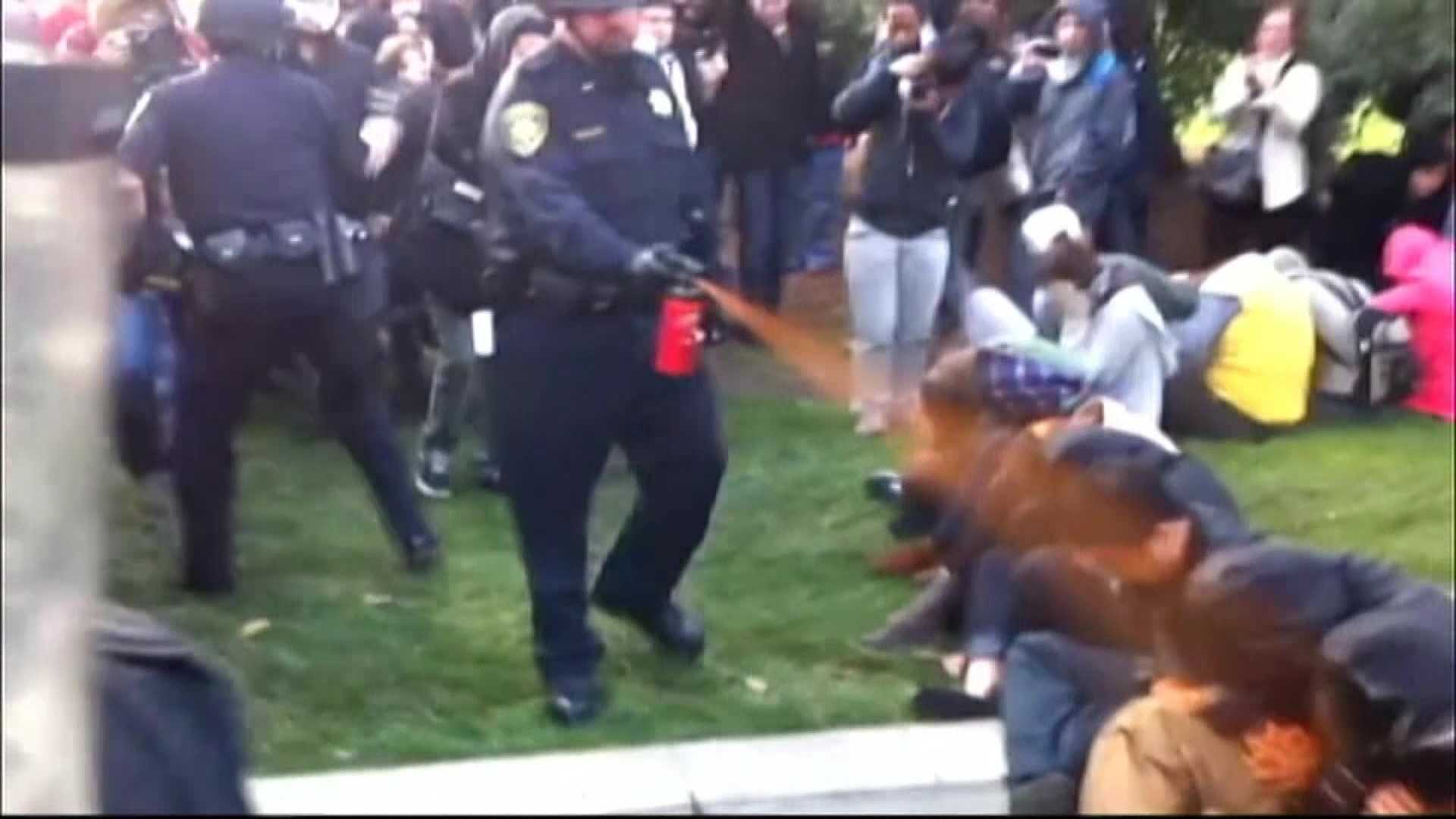 A UC Davis campus police officer pepper sprays student protesters in November 2011.
