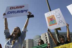 Women hold up signs protesting Donald Trump outside of the Hyatt Regency hotel before the California Republican Party 2016 Convention in Burlingame, Calif., Friday, April 29, 2016
