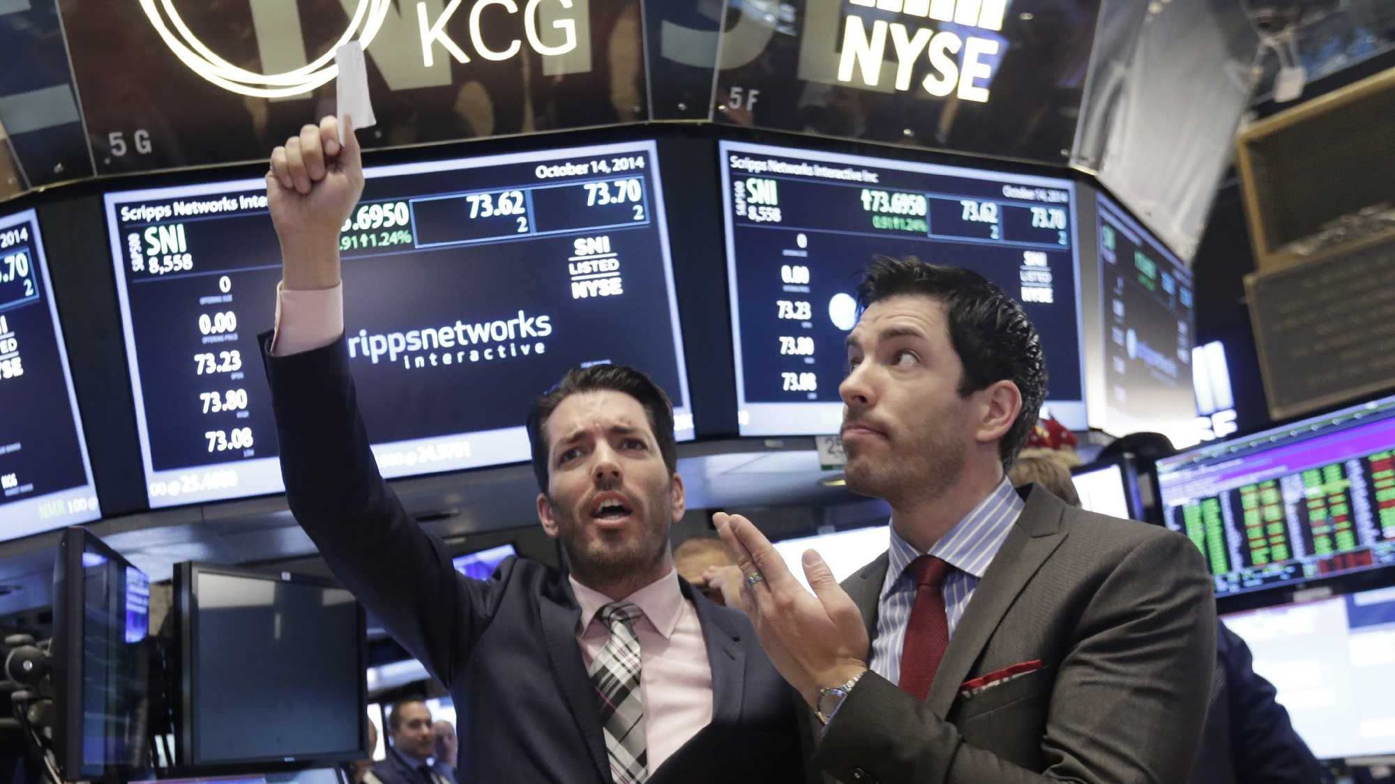"In this Oct. 14, 2014, file photo, Jonathan Scott, left, and Drew Scott, of HGTV's ""Property Brothers"" cable television show, mimic traders on the floor of the New York Stock Exchange."