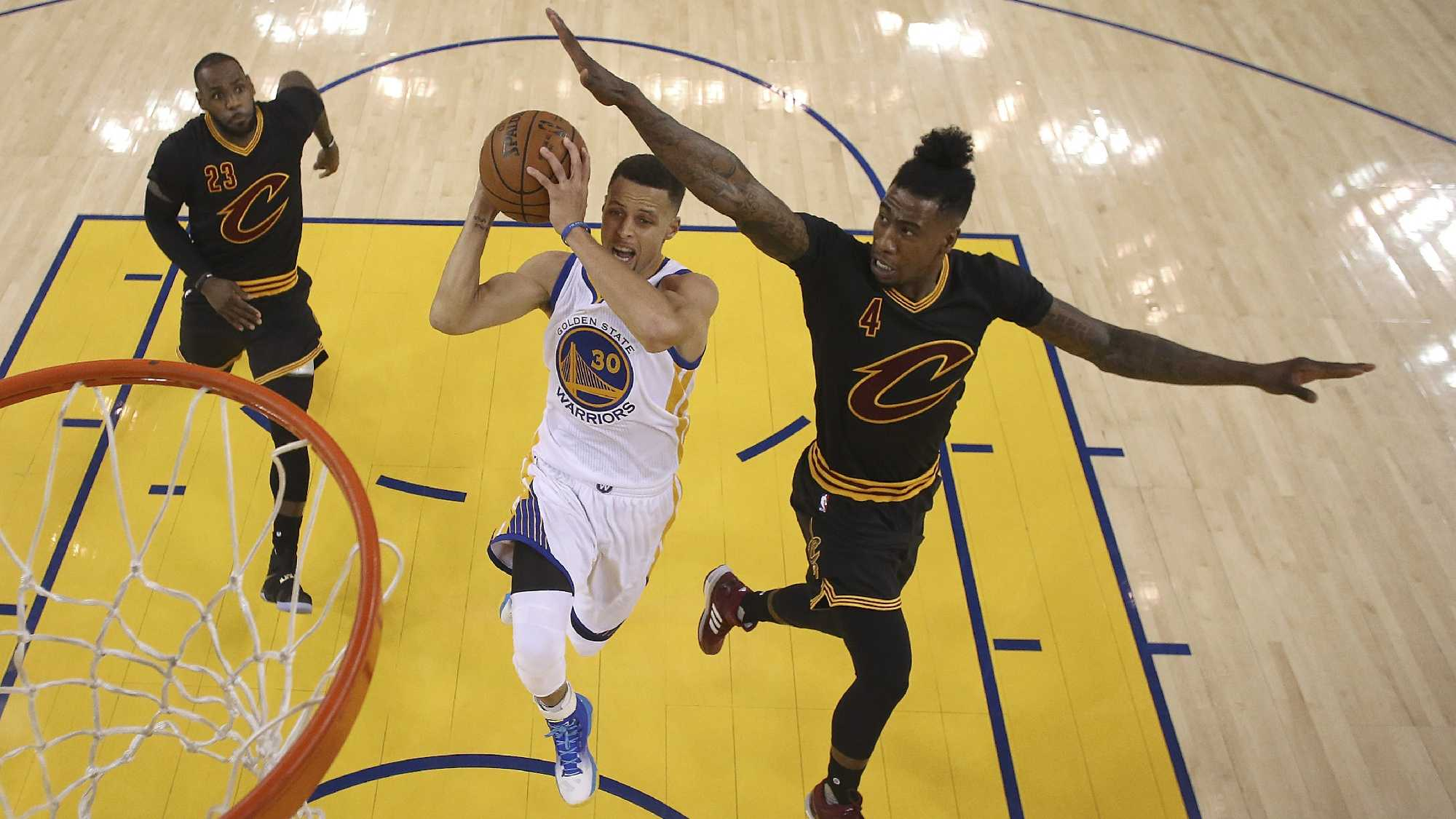 Golden State Warriors guard Stephen Curry (30) shoots between Cleveland Cavaliers forward LeBron James (23) and guard Iman Shumpert (4) during the first half of Game 5 of basketball's NBA Finals in Oakland, Calif., Monday, June 13, 2016.