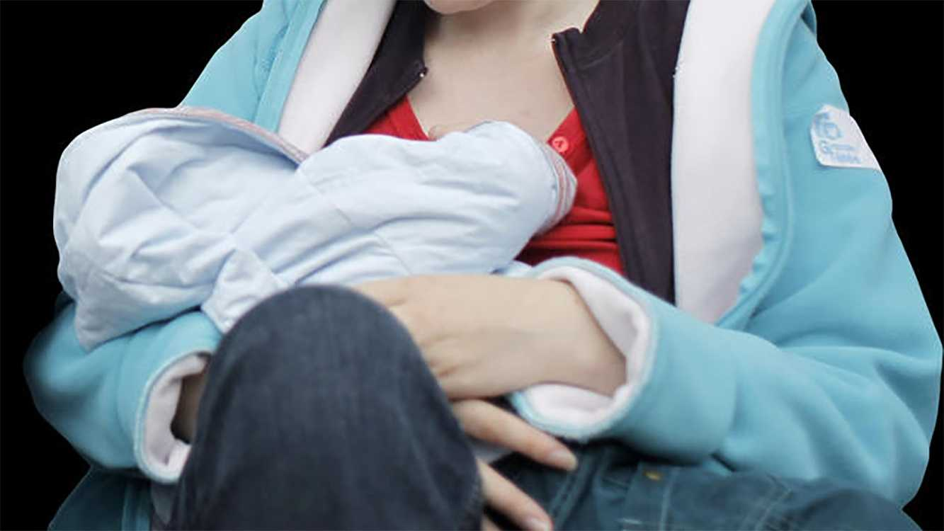 Woman breastfeeds baby