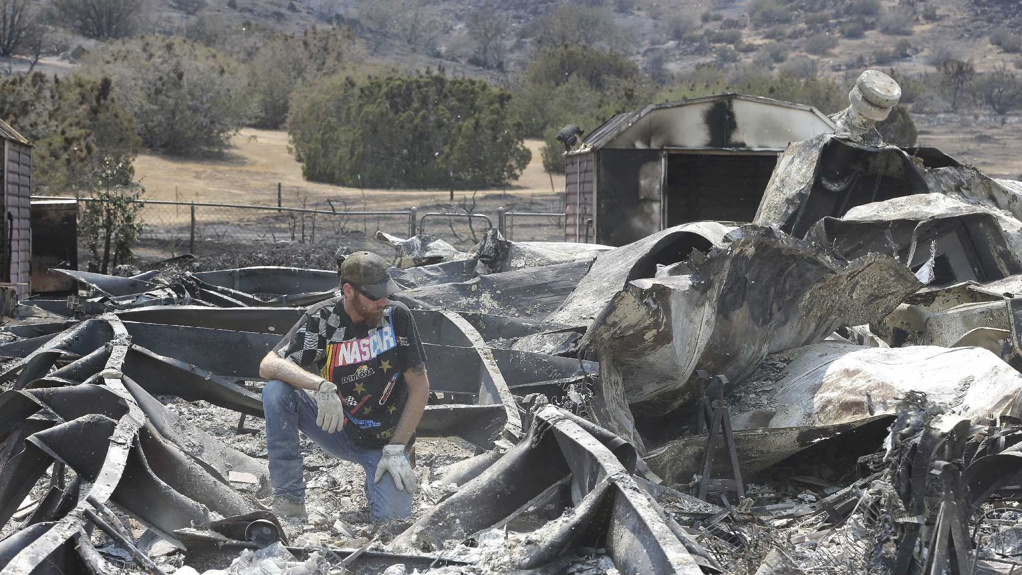 Lucas Martin stares at all that remains of his fire ravaged home in South Lake, Calif., Sunday, June 26, 2016. Martin's home was among the more than 200 homes and buildings destroyed by the fire that swept through the area near Lake Isabella, Calif.