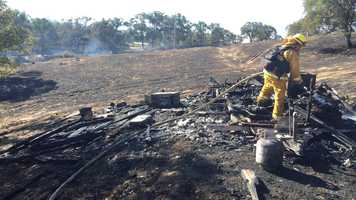 Fire crews mop up trailer burned in Stagecoach Fire.
