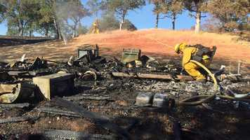 Fire crews clean-up trailer burned in Stagecoach Fire.