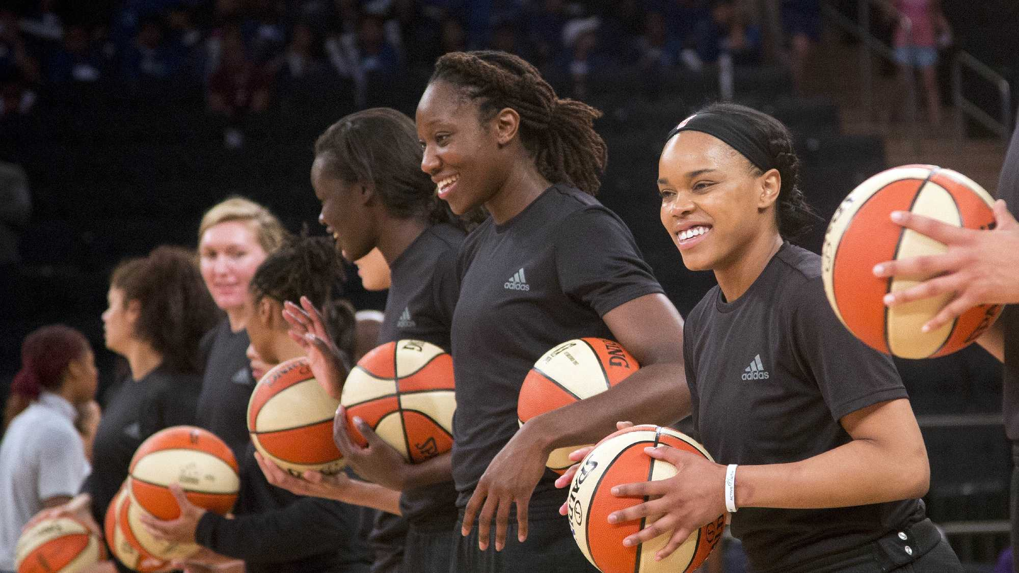 In this Wednesday, July 13, 2016 file photo, members of the New York Liberty basketball team await the start of a game against the Atlanta Dream, in New York. The WNBA has fined the New York Liberty, Phoenix Mercury and Indiana Fever and their players for wearing plain black warm-up shirts in the wake of recent shootings by and against police officers. All three teams were fined $5,000 and each player was fined $500. While the shirts were the Adidas brand - the official outfitter of the league - WNBA rules state that uniforms may not be altered in any way.