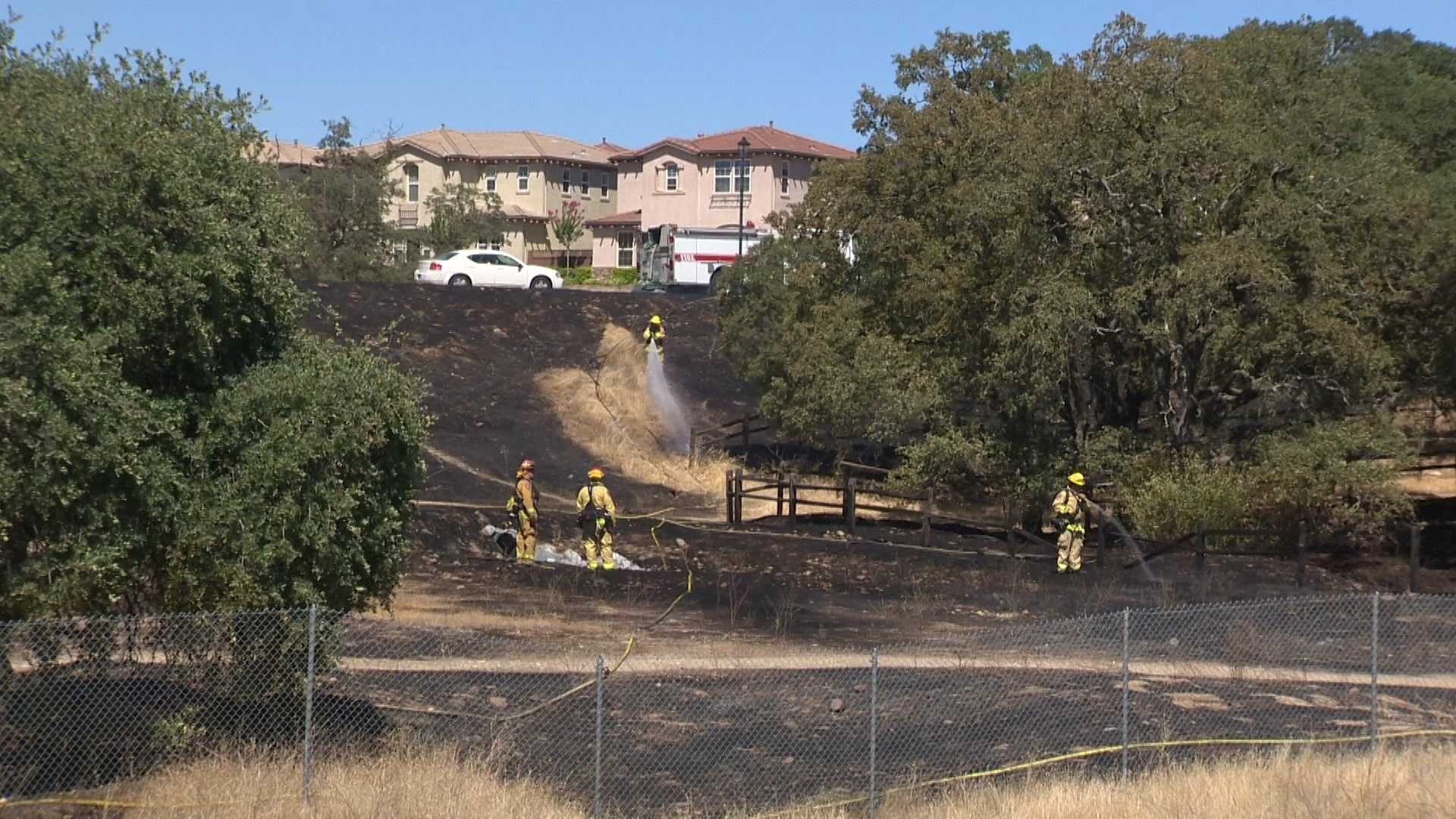 Firefighters mop up after a 3-acre grass fire in Folsom on Saturday, July 23, 2016.