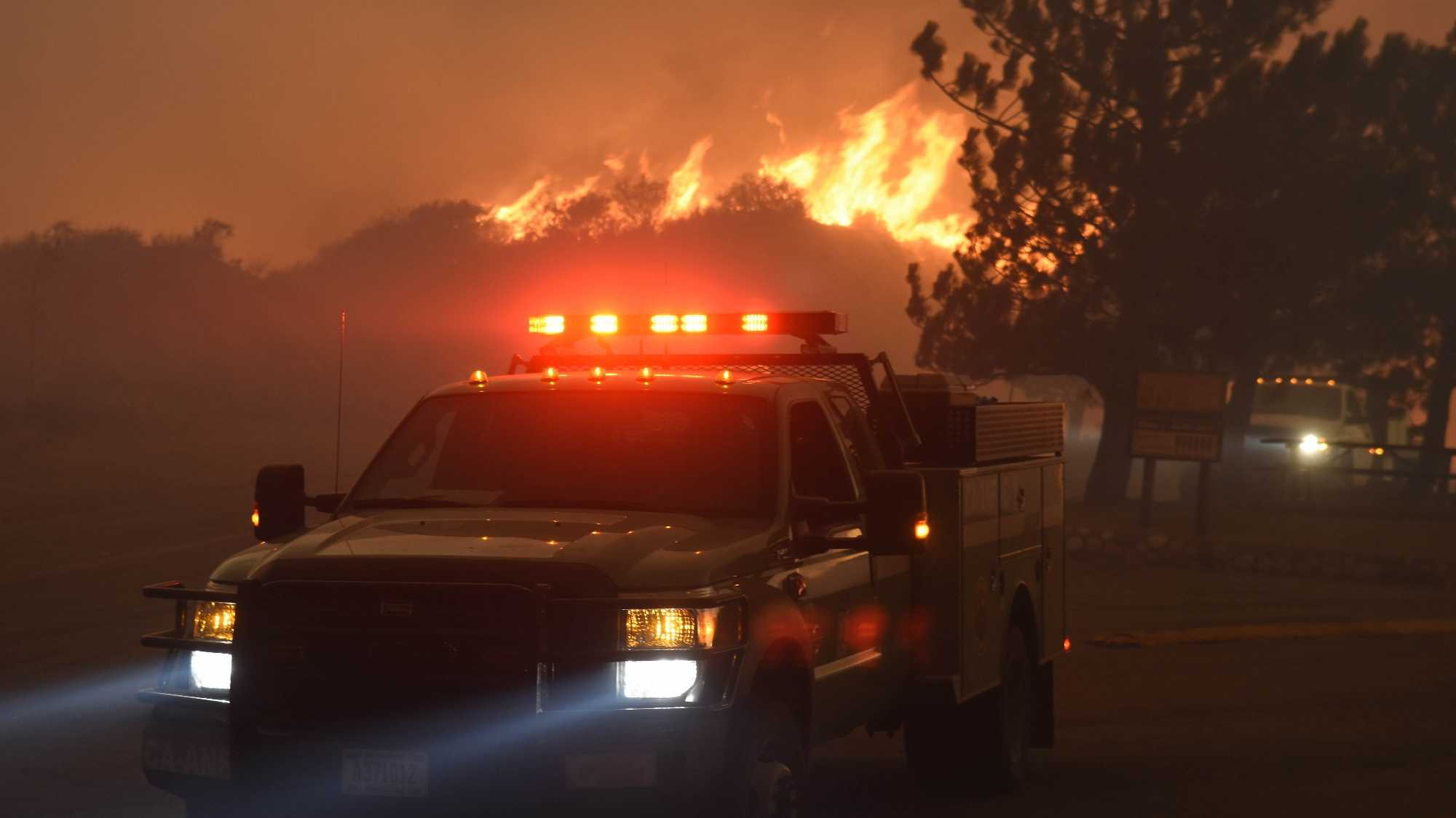 A fast burning wildfire chases down a couple of engines down Sand Caynon, near the Bear Divide in the Angeles National Forest, Calif., Saturday, July 23, 2016.