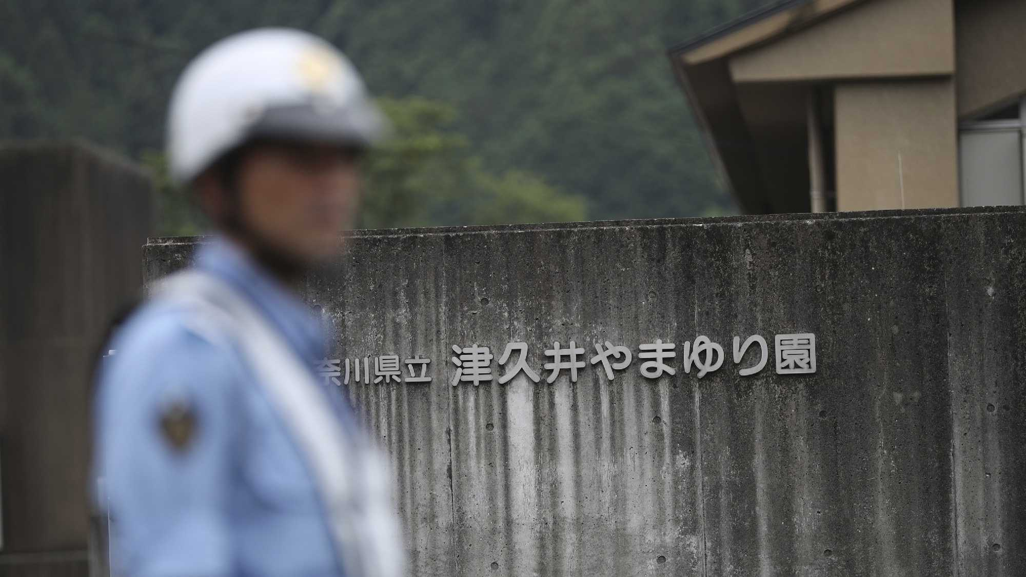 A police officer stands guard at the gate of Tsukui Yamayuri-en, a facility for the handicapped where a number of people were killed and dozens injured in a knife attack in Sagamihara, outside Tokyo Tuesday, July 26, 2016. Police said they responded to a call about 2:30 a.m. Tuesday from an employee saying something horrible was happening at the facility. A man turned himself in at a police station about two hours later, police said.