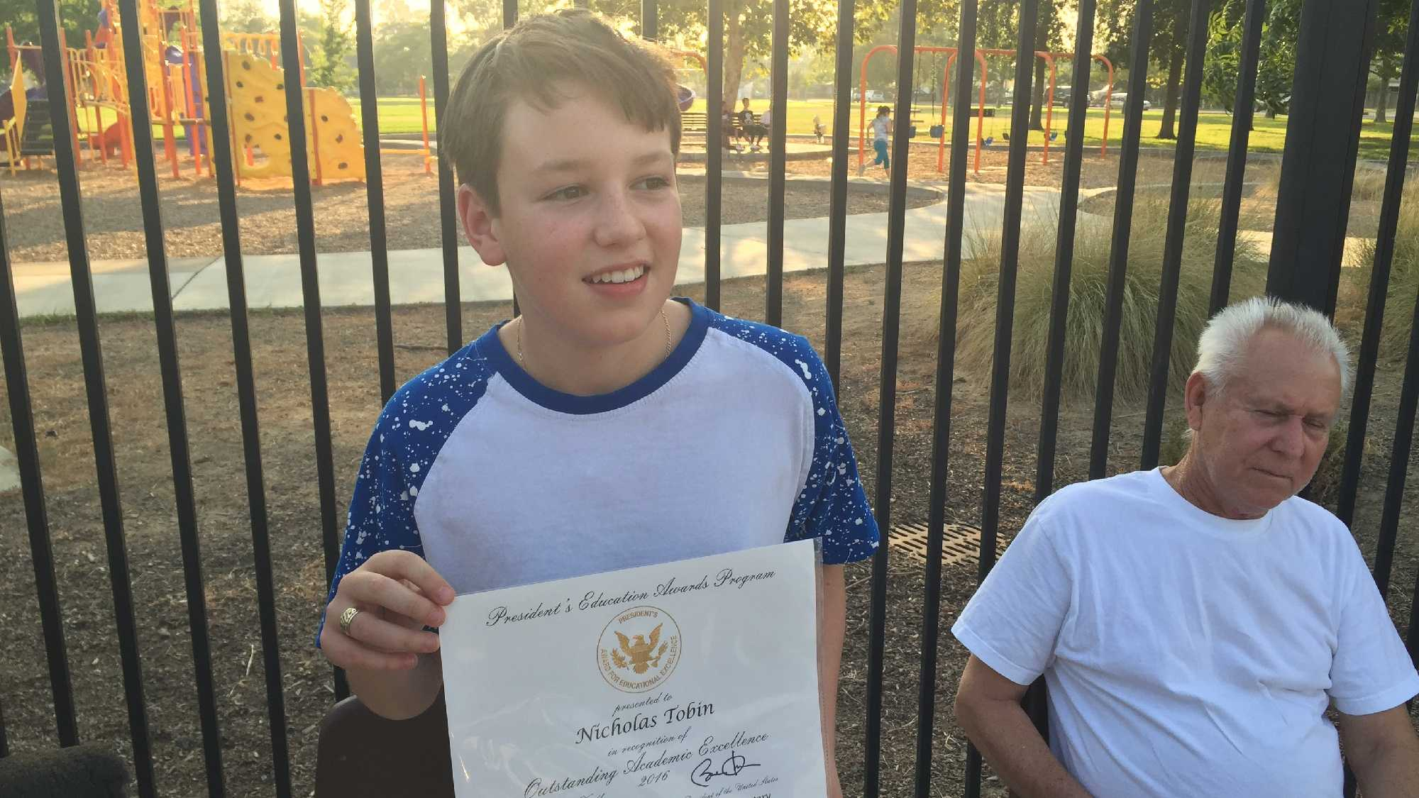 Nick Tobin, 12, holds up his certificate of outstanding academic excellence from President Obama on Wednesday, July 27, 2016.