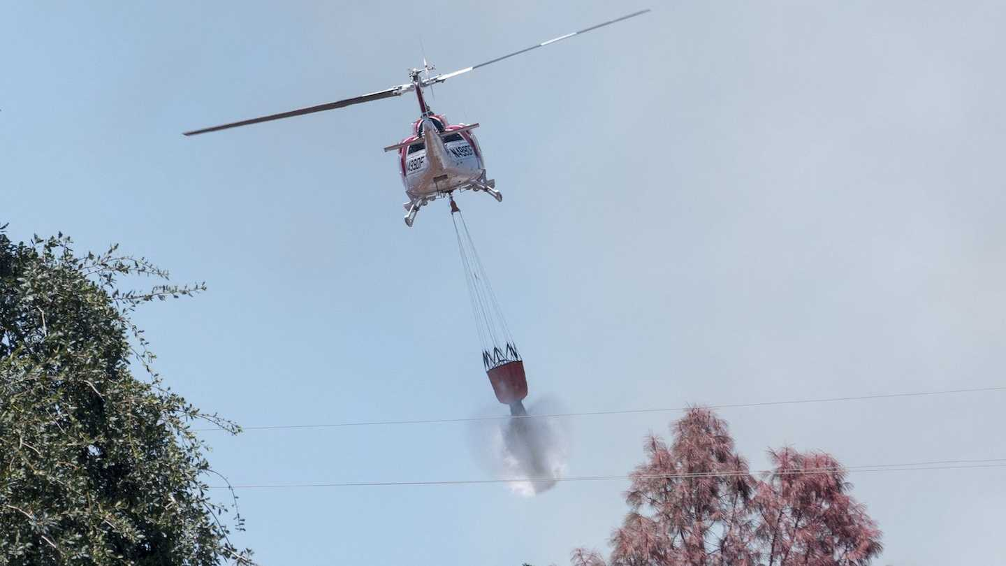 A helicopter drops water over a wildfire burning in Clearlake on Friday, July 29, 2016.