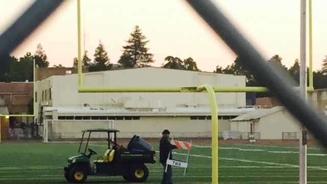 Worker puts up barrier on turf of Joe Debely Stadium in Turlock.
