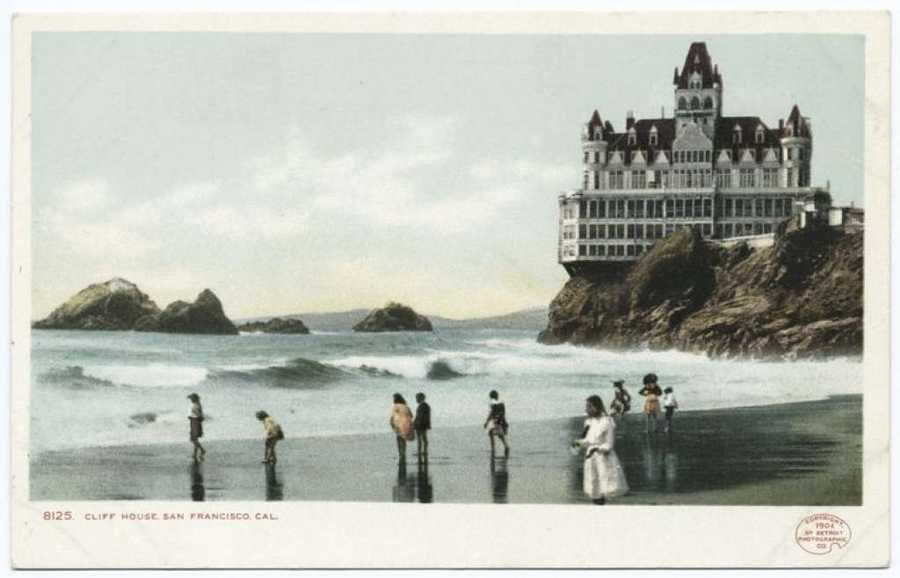 A postcard from the Detroit Publishing Company shows beach-goers enjoying the surf near the Cliff House in San Francisco.