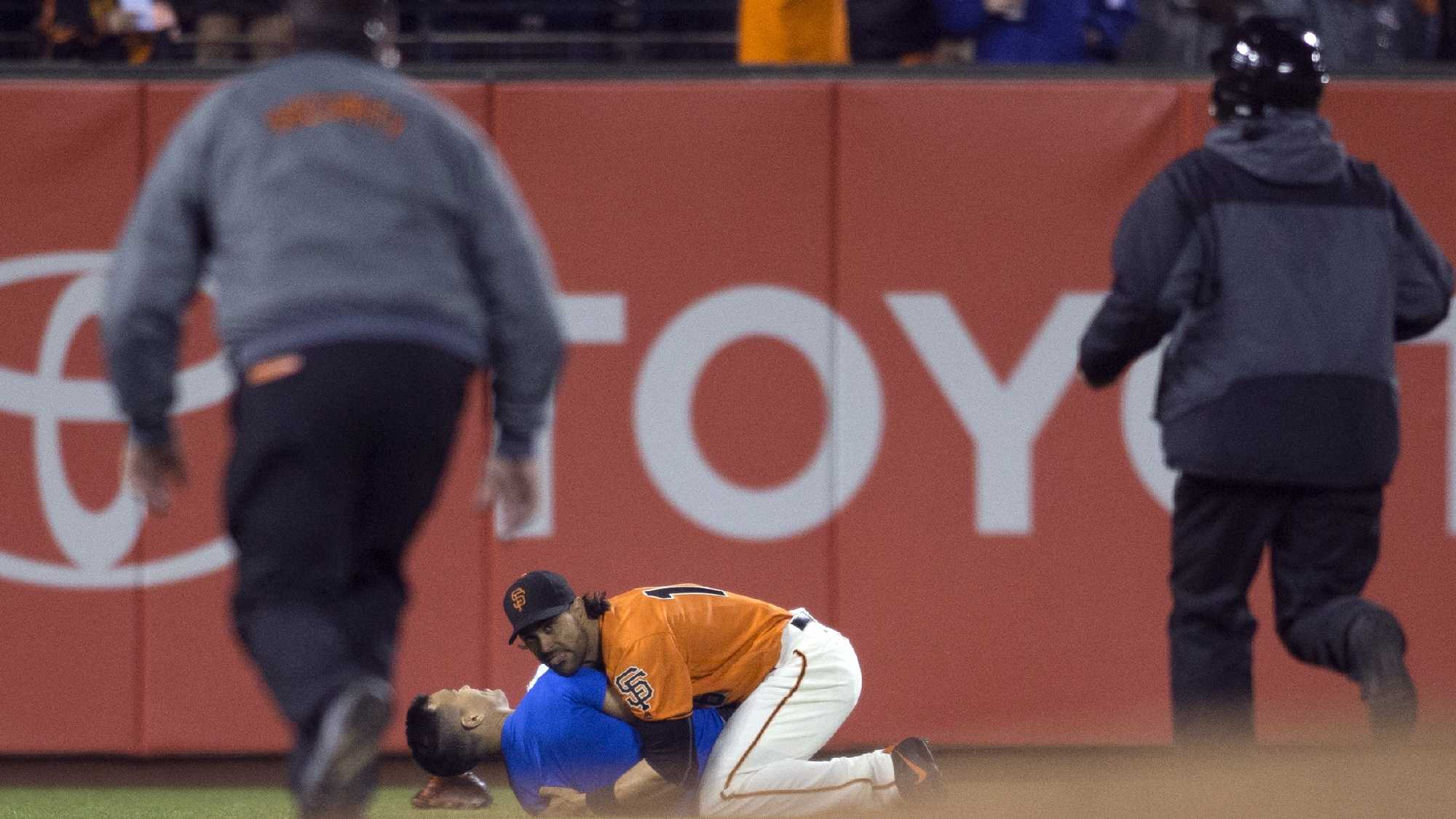 San Francisco Giants' Angel Pagan (16) holds down a man who ran onto the field during the fourth inning of the Giants' baseball game against the Los Angeles Dodgers, Friday, Sept. 30, 2016, in San Francisco.