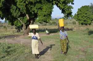 Each day women in Kadi make multiple trips to get water from a well. They balance the jugs on their head. The jugs weigh about 40 pounds each. The walk can be up to four blocks away.