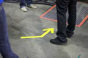 Bright-colored arrows taped onto the ground help the band get to the stage.