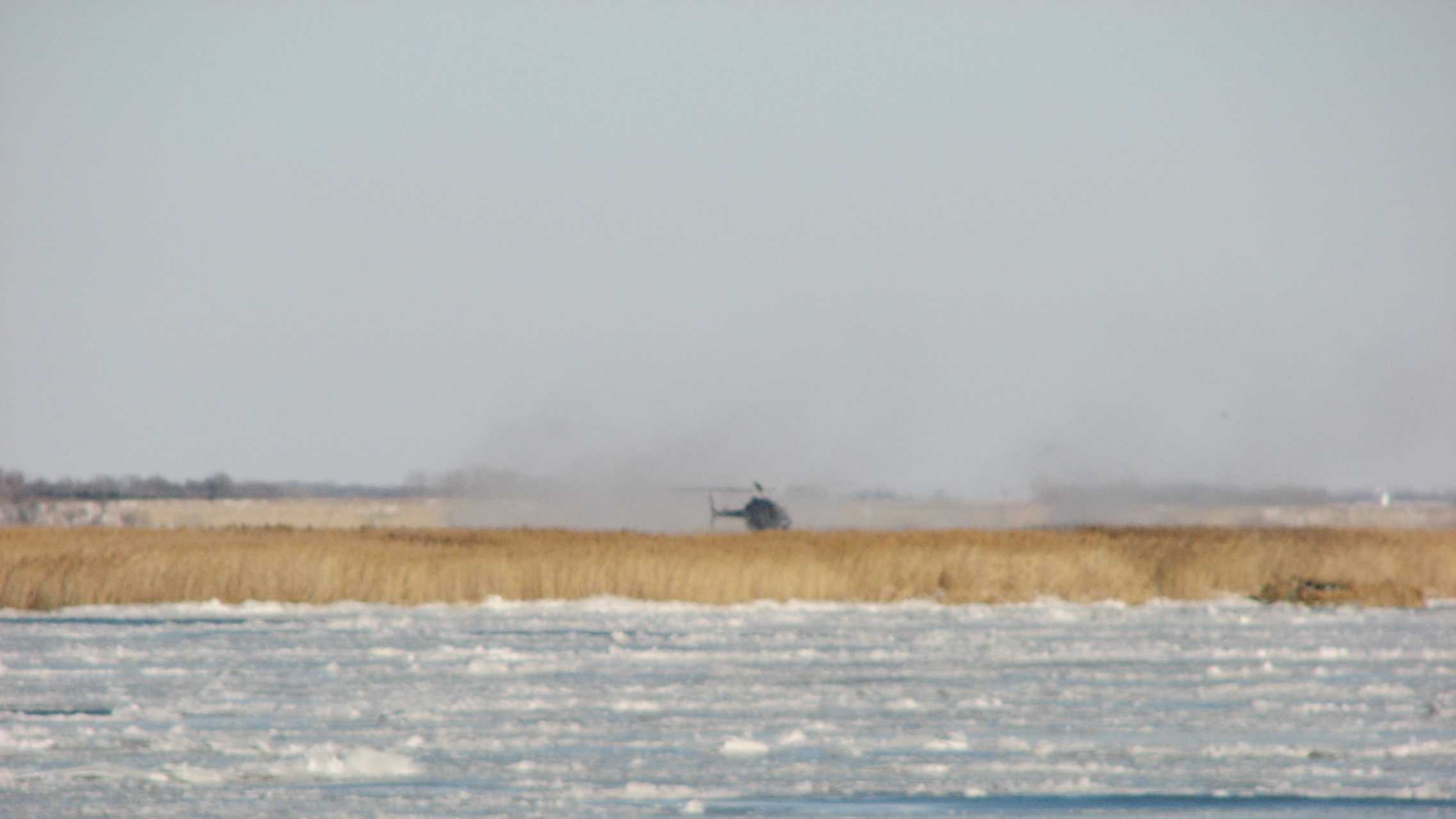 NSP helicopter landing on the marsh island to rescue the hunters.
