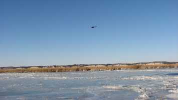 NSP helicopter hovering over marsh island preparing to rescue stranded hunters