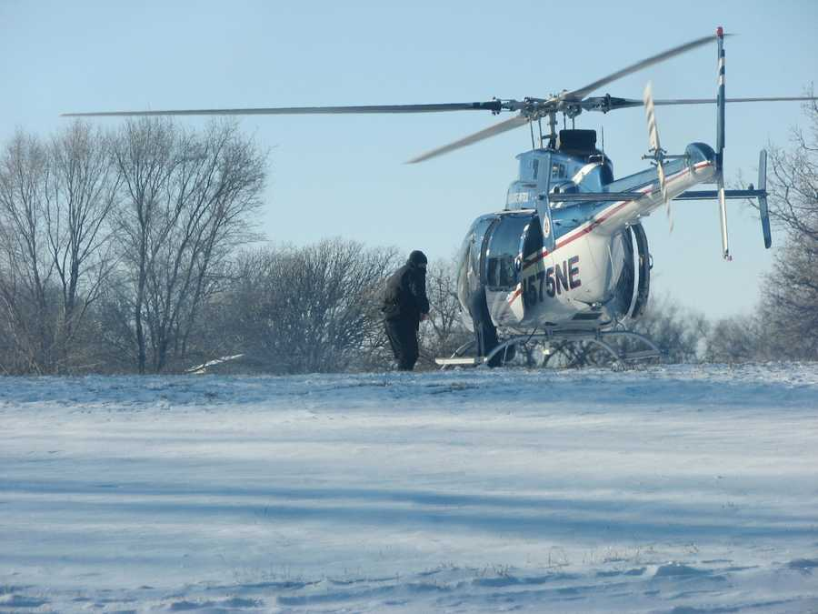 NSP pilot Sgt. Brian Petersen opening helicopter doors for two rescued hunters to disembark from helicopter
