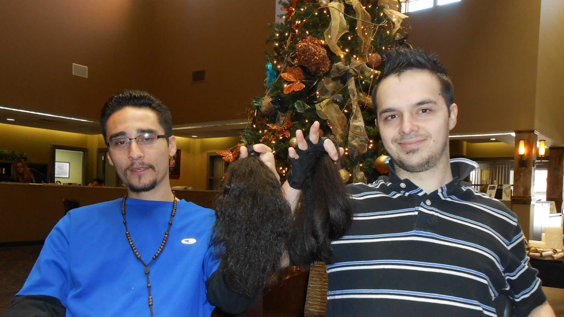 Dave Dominguez and Aaron Tanguis show off the hair they're donating to Locks of Love.  Great Clips provided free haircuts for both men.