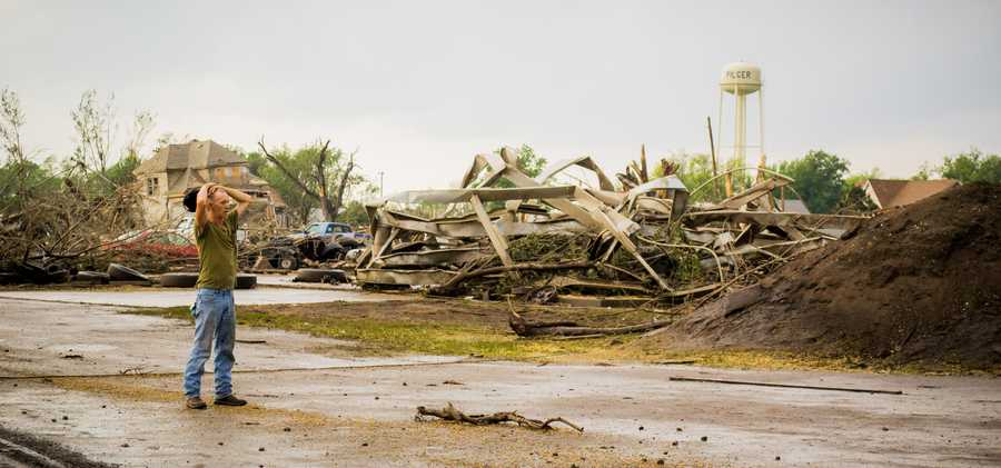 A man stands and takes in the destruction after a tornado destroys half of the town of Pilger, NE on 6/16/14.