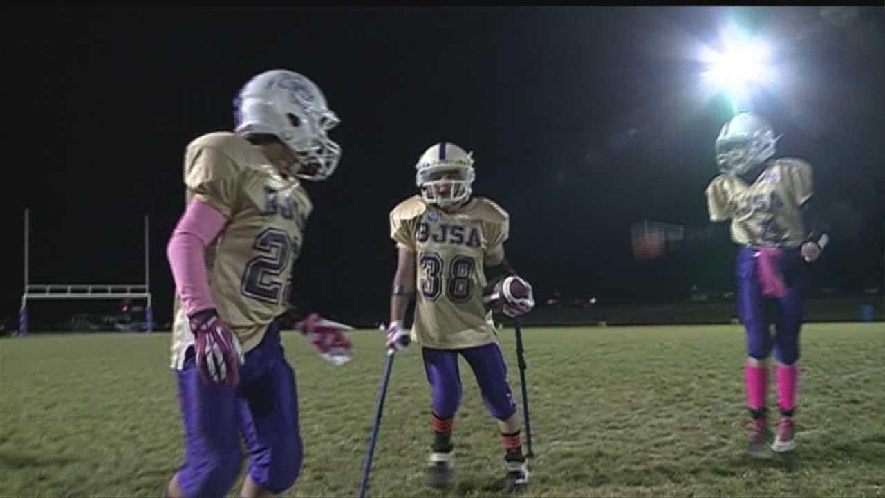 Team members help Austin Cooper make touchdown