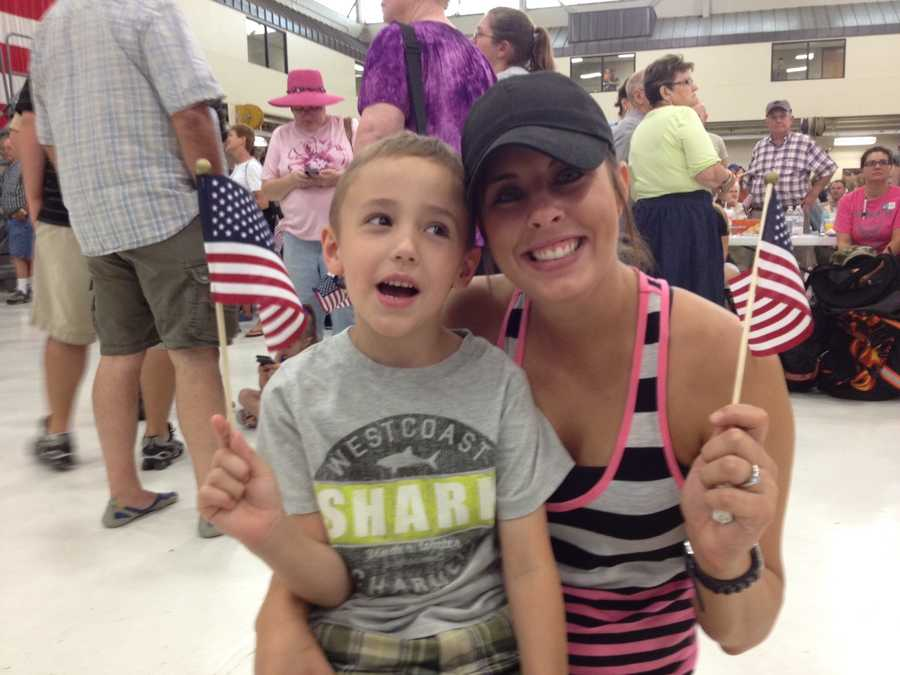 Wife and son cheer on their hero as he was being deployed in July.