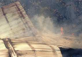 Five fire departments battle a storage shed blaze and grass fire in Muldrow, Okla.