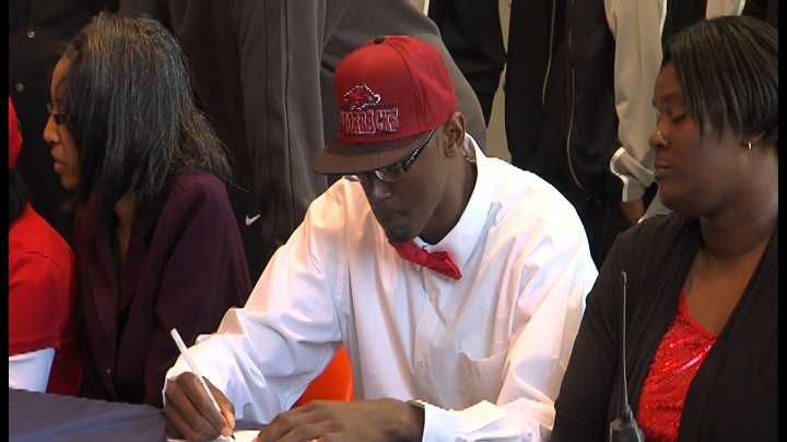 Wearing a Razorbacks hat, Little Rock Hall center Bobby Portis signs his national letter of intent to play for the University of Arkansas