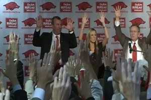 """Arkansas head football coach Bret Bielema """"calls the Hogs"""" with wife Jen and Athletic Director Jeff Long for the first time."""