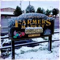 A snowy Farmers Market sign in Rogers.