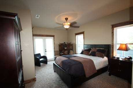 The bedroom has plenty of natural light pouring in from multiple windows and French doors leading outside.