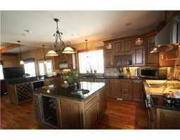 A country kitchen with modern appliances and breakfast bar is convenient and perfectly equipped for family needs.