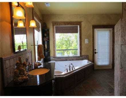 The master bath has multiple mirrors for getting ready in the morning, but it also has a television mount visible from the bathtub, perfect for soaking and unwinding from a long day.