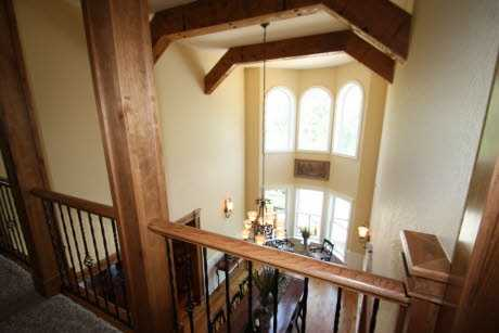 The upstairs hallway is open and overlooks the dining room.