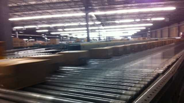 Boxes zoom along a 12-mile long conveyor belt during the shareholders' tour Thursday. Wal-Mart moved more than 5.5 billion cases last year worldwide.