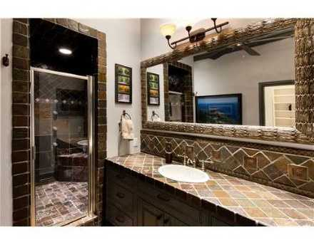 Take a look at this gorgeous bathroom with updated fixtures, extra counter space, and a floor-to-ceiling tiled shower.