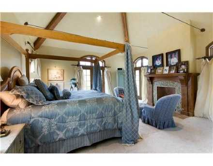 This beautiful master suite has everything one would need for a perfect getaway. It has dark, natural wood trim, a fireplace, high-ceilings with exposed beams, oversized windows, and walk-out doors that lead to a serene outdoor overlook.