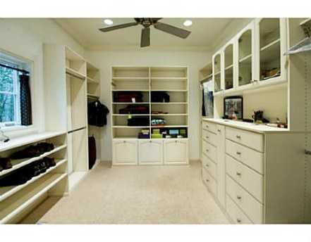 Natural light, beautiful white cabinets and shelves make this walk-in-closet a dream.