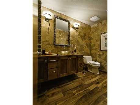 This bathroom is the epitome of modern luxurious style with elegant golden walls, a waterfall sink faucet, a raised sink, exposed brick, and beautiful wood floors.