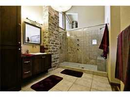 This beautiful, spacious bathroom with exposed brick and natural lighting will leave you calm and relaxed at the end of the day.