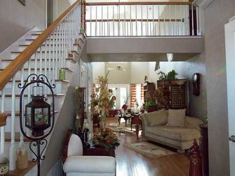 The entry way leads either upstairs that is open overlooking the living room or to the living room itself. The high ceilings and open area gives a sense of roominess and connectivity.
