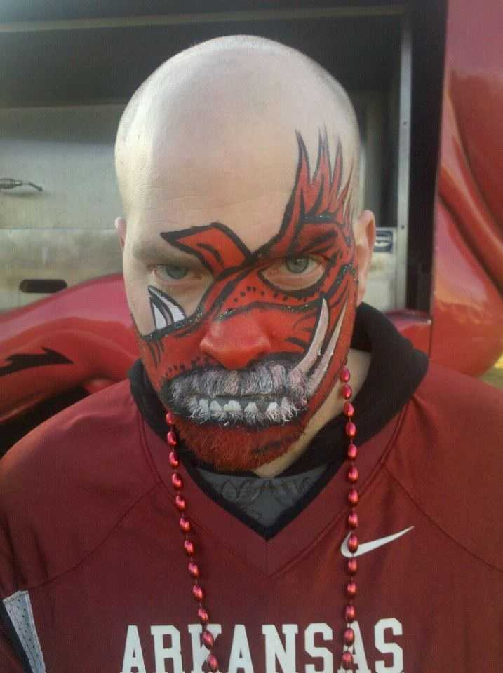 These are pictures of my husband Jamie at last year's homecoming game. In these pictures he has the side profile of a Razorback painted across his face and he's cheering on his Hogs with those pom poms